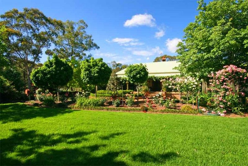 Beautiful established gardens with park-like lawns plus an elegant country home privately situated on a wide 5 acre block.
