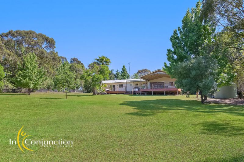 Picturesque 5 acre property with light-filled single level home showcasing stunning outdoor deck overlooking the rolling acres and lovely dams