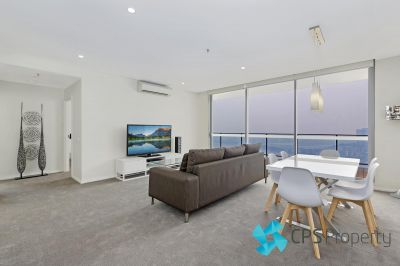 TOP-FLOOR TWO BEDROOM RESIDENCE COMMANDING PANORAMIC WATER VIEWS