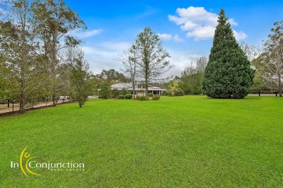 stunning smaller acreage property with renovated home, light filled rooms with high ceilings -elevated setting with views over lake-like dam.